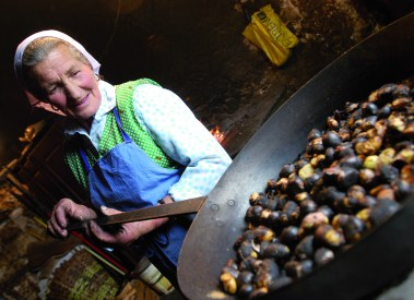Chestnuts roasted in a large pan over an open fire
