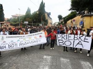 """Les gens se rassemblent devant l'église de Lefebvriani pour protester avec une bannière qui dit: """"Bourreau Priebke"""" la semaine dernière à Albano Laziale, Italie."""