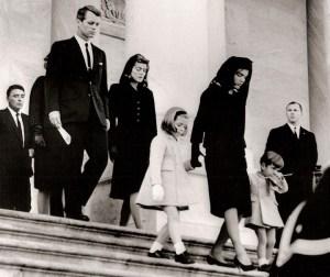 La famille Kennedy quitte la cathédrale Saint-Mathews après les funérailles. Le corps du président Kennedy est alors pris au cimetière national d'Arlington pour l'enterrement.