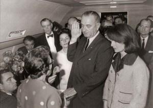 À 14h38 à bord d'Air Force One, Lyndon B. Johnson est assermenté à titre de 36e président des États-Unis, tandis que Jacqueline Kennedy observe. Air Force One enlève ensuite avec le corps du président tué à bord.