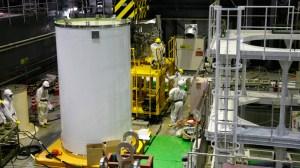 Ouvriers vérifient un conteneur de transport et une grue en vue de l'élimination du combustible nucléaire irradié de la piscine de combustible usé à l'intérieur du bâtiment du réacteur n ° 4 à (TEPCO) Fukushima Daiichi centrale nucléaire de tsunami paralysé de la Tokyo Electric Power Corp, à Fukushima