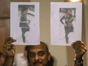 Un officier de police malaisienne détient photos de deux personnes censées être les passagers qui avaient volé des passeports sur la Malaysia Airlines vol a disparu