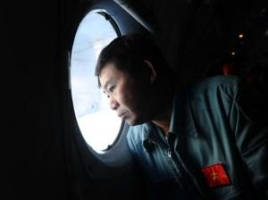 """Un militaire vietnamien scrute scrute l'immensité à bord d'un AN-27 survolant la zone de recherche de l'avion Malaysia Airlines disparu, vendredi 14 mars. Les recherches se sont étendues à l'Océan indien, après de """"nouvelles informations"""" citées par la Maison Blanche suggérant que l'appareil a continué de voler pendant plusieurs heures après sa disparition des écrans radar. (HOANG DINH NAM/AFP)"""