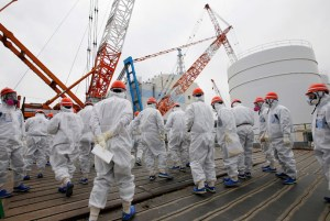 Members of the media and Tokyo Electric Power Co. (TEPCO) employees wearing protective suits and masks walk toward the No. 1 reactor building at the tsunami-crippled TEPCO's Fukushima Daiichi nuclear power plant in Fukushima prefecture March 10, 2014.