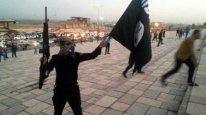 Un combattant de l'Etat islamique d'Irak et du Levant (ISIL) tient un drapeau de ISIL et une arme dans une rue de la ville de Mossoul