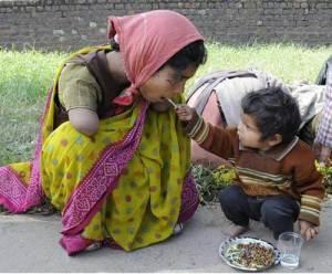 Un jeune garçon aide sa mère à se nourrir au moyen de baguettes.Sa mère qui a perdu ses deux bras malheureusement.