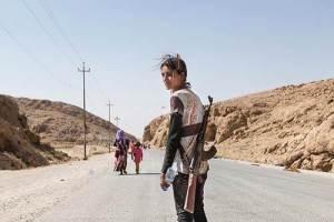 Cette jeune fille yézidie (chrétienne du nord de la Syrie) protège sa famille des attaques terroristes de l'État Islamique,au moyen d'un fusil AK-47.