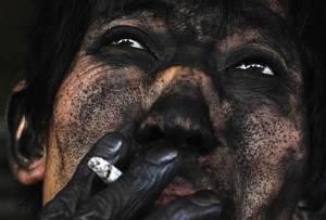 Le visage crasseux d'un jeune mineur chinois ,dans une mine de charbon.Regardez ses mains qui ressemblent à celles d'un vieil homme.