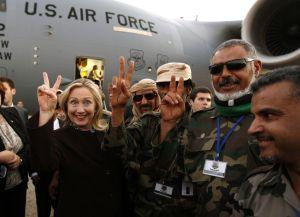 """Hillary Clinton est cette politicienne américaine qui a particulièrement aidé à l'instauration de la """"Pax Americana"""" en Lybie.On la voit ici,le 19 octobre 2011,faisant son signe illuminati de la victoire,entourée des mercenaires terroristes qu'elle a grassement payé pour éliminer le Grand Guide Lybien Khadafi et mettre ce pays en ruines."""
