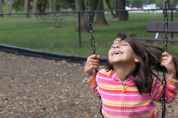 Day 277 I've learned to focus on the swinging child's face, wait for her to complete another swing, and *then* click the shutter when she returns to the point at which I had focused.  Av f/6.3 1/160sec