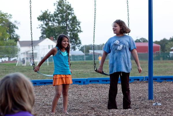 Day 214  Singing At The Park  -- Rhiannon was just sitting on the swing singing and she caught the attention of a whole group of people doing their own activity nearby.  When they asked her to sing more, she asked Caroline to join her.  They had a great time.  50mm  Manual   ISO200  f/3.2  1/400sec  I increased the exposure and fill light in Lightroom.