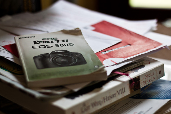 Day 219 Something I read in a photography tutorial inspired me to pick up my camera to check something, exactly what I've forgotten now, but I like how this looks, some stuff currently stacked on my desk.  50mm  Manual   ISO400  1/200sec  f/2.2   I increased the contrast, clarity, vibrance, and decreased the noise a bit in Lightroom, just for fun.