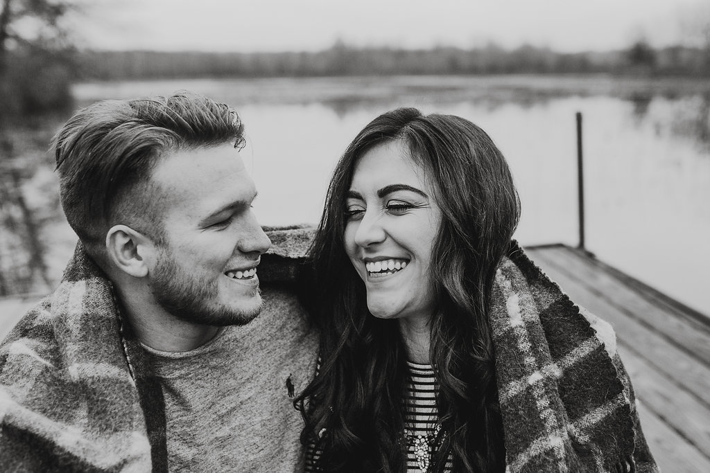 A lake engagement photo of a couple leaning in close, wrapped in a blanket, sharing a laugh, on a dock