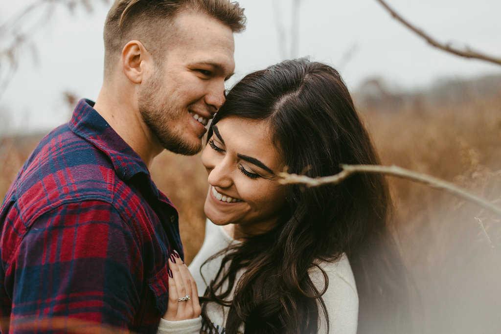 A laughing couple lean in towards each other in a golden field in this fall engagement photo.