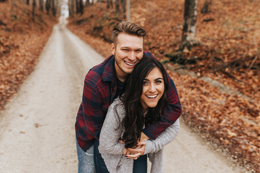 Autumn Engagement Photo of a couple interacting playfully on a path surrounded by fallen leaves in Bloomington, Indiana.