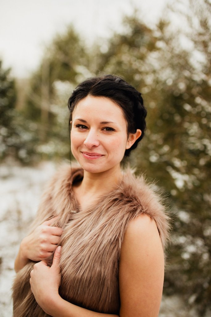 A winter portrait of a smiling woman wearing a fur vest against a snowy forest background.