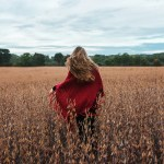 A girl in a red shawl spins in a golden field. Her blonde hair mimics the movement of her cape.