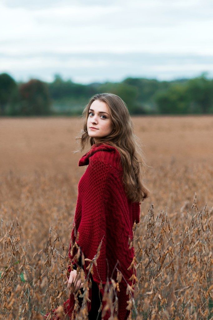 Hanna | A girl with blonde hair and blue eyes looks back over her shoulder while standing in a golden field. She is wearing a red shawl on an overcast day in the Morgan Monroe State Forest.