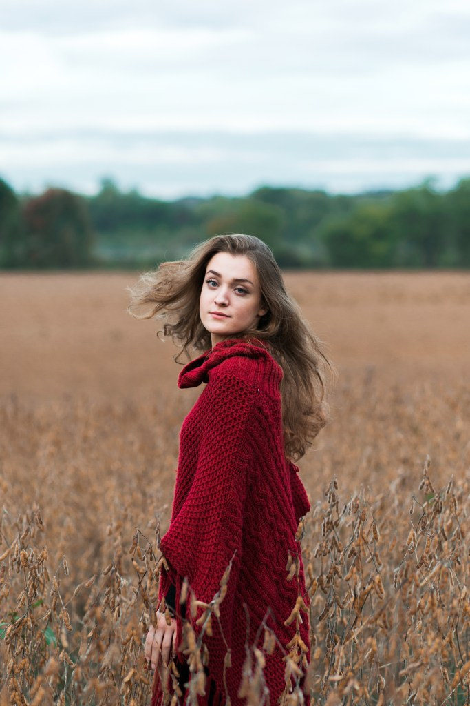 Hanna | A girl in a red shawl spinning in a golden field. Her blonde hair mimics the movement of her cape.