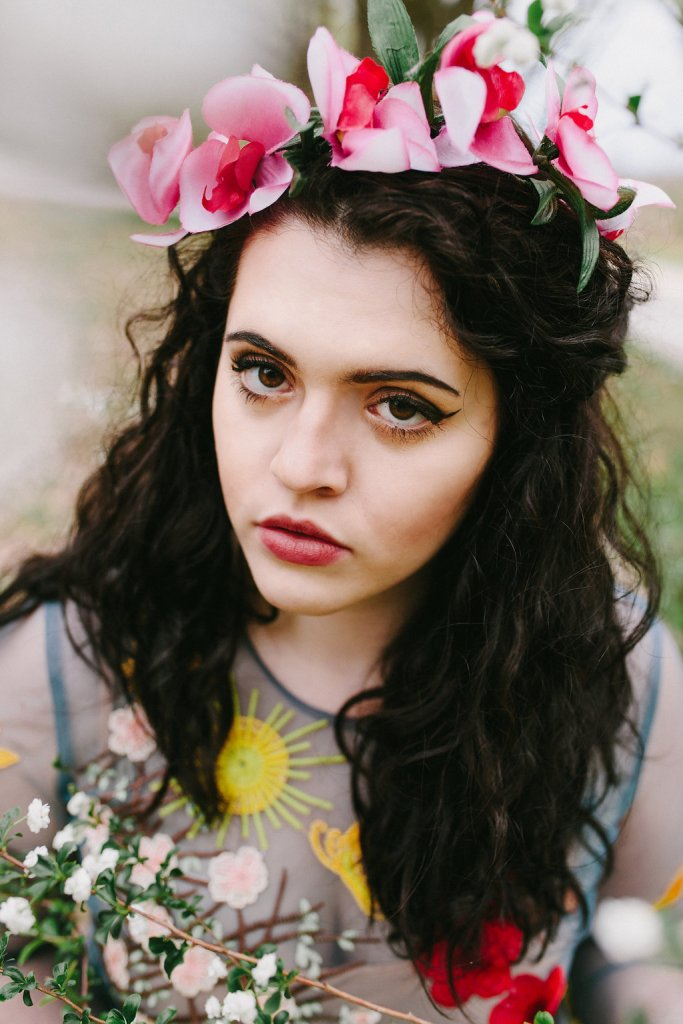 A girl with dark, curly brown hair, chocolate brown eyes, and a cat eye makeup wearing an orchid flower crown is amongst some baby's breath flowers in the spring. She is wearing a sheer blue dress covered in floral embroidery.