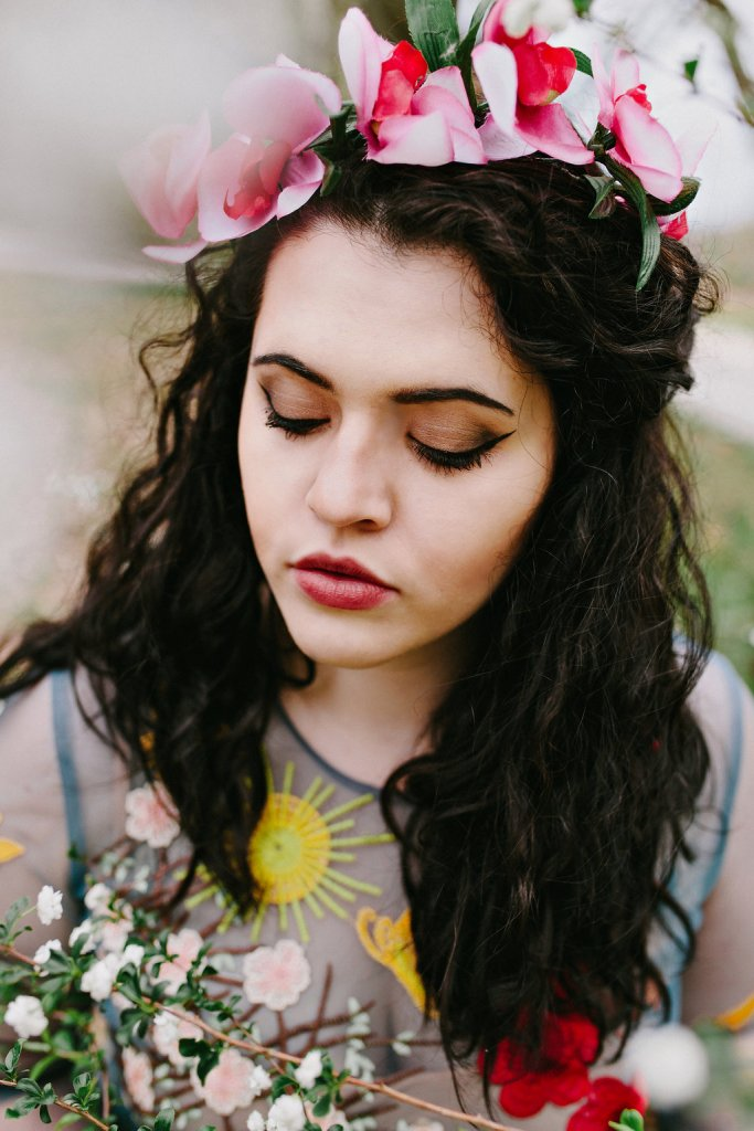 A girl with dark, curly brown hair and a cat eye makeup wearing an orchid flower crown is amongst some baby's breath flowers in the spring. She is wearing a sheer blue dress covered in floral embroidery.