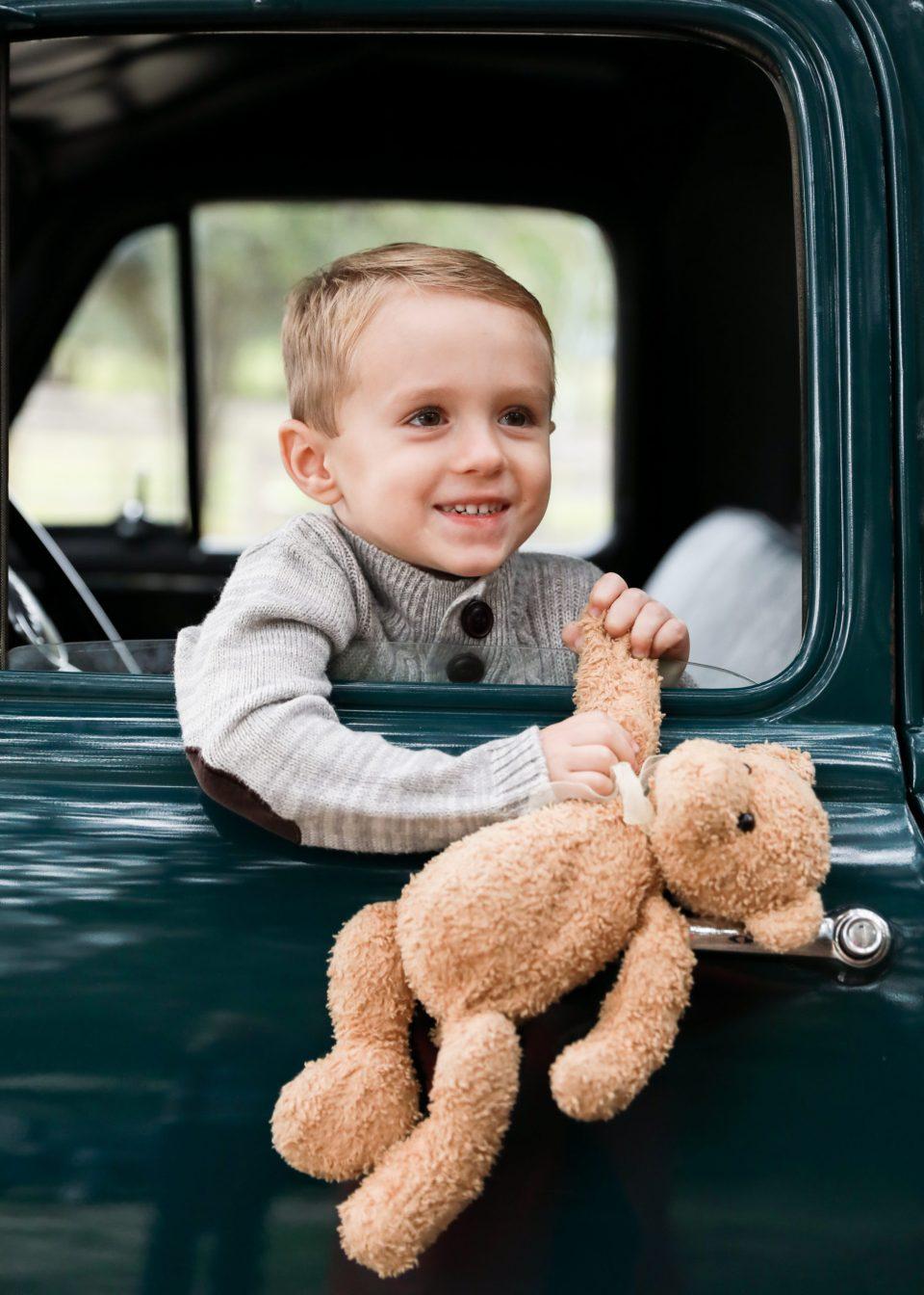 Cute boy with bear in truck