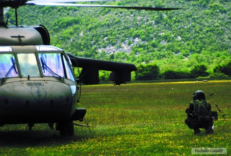 A refueling technician waits as a Blackhawk is filled with gas between flights. Fuel was carried by helicopters to the mission site in 500-pound fuel bladders.