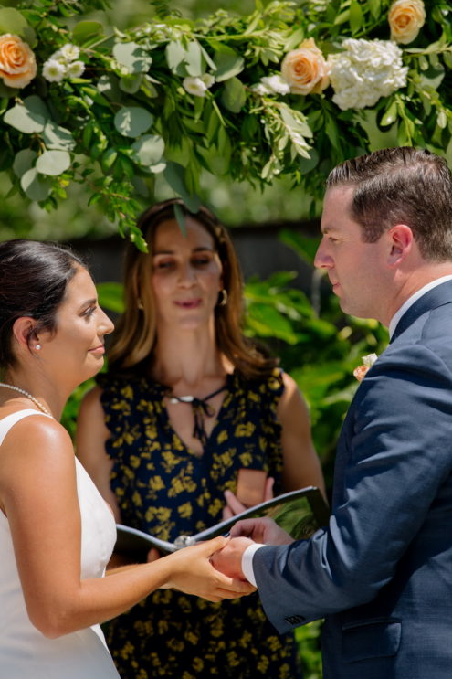 couple getting married under arbor in their backyard