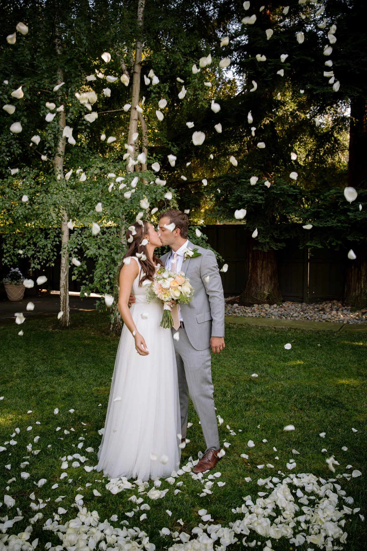 couple kissing after throwing rose petals