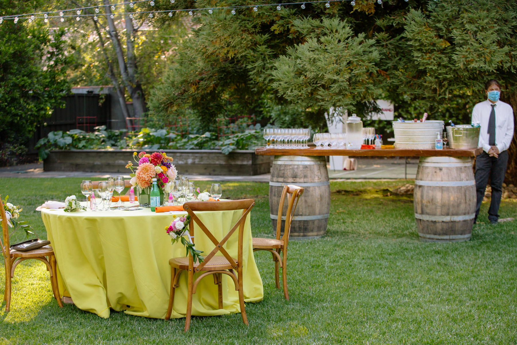 lemon yellow linens and colorful flowers at this backyard wedding