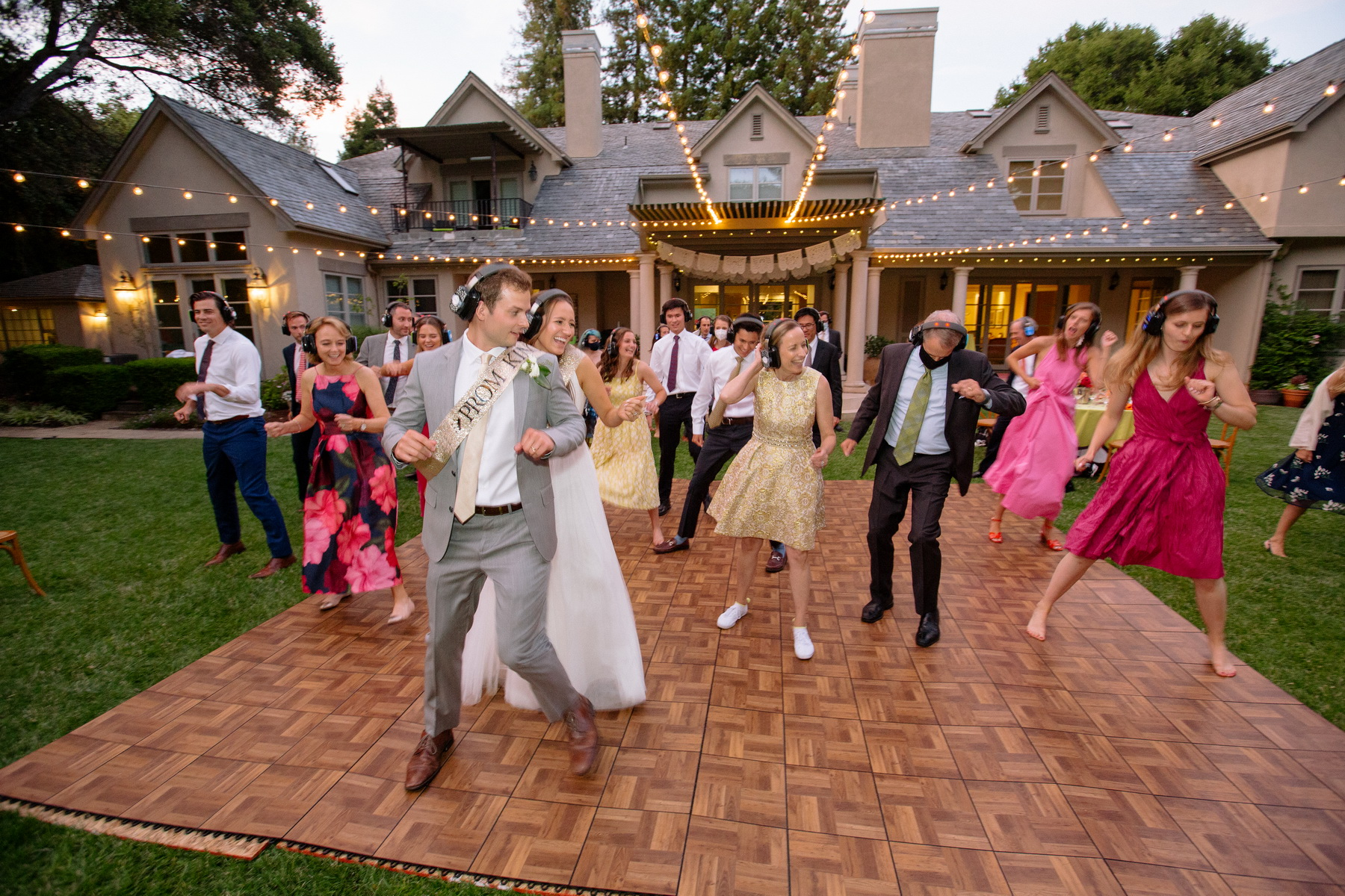 guests dancing to a silent disco at a backyard wedding