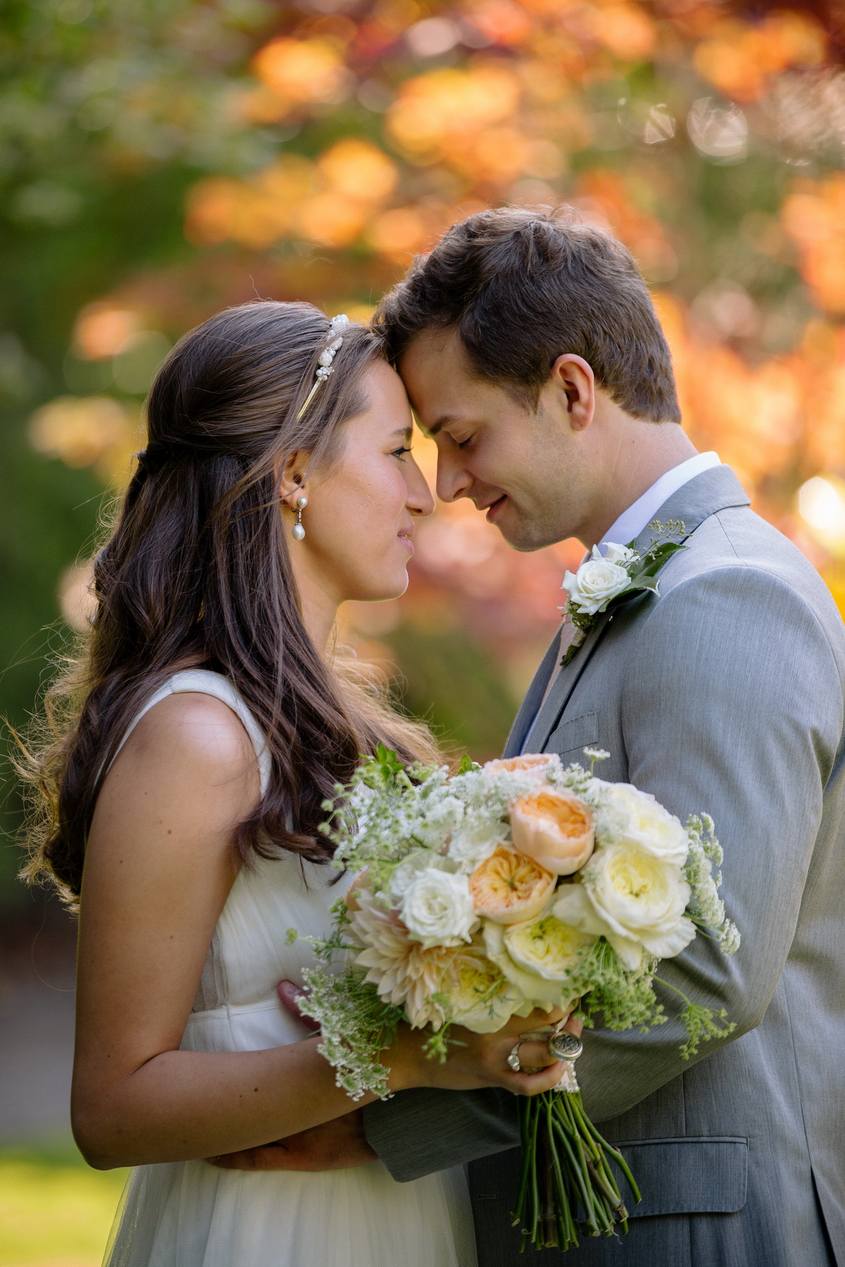 casual portrait of a bride and groom with fall foliage