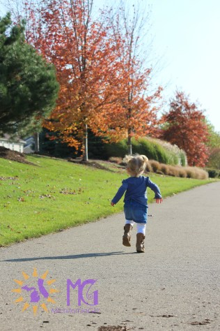 little girl running in the fall
