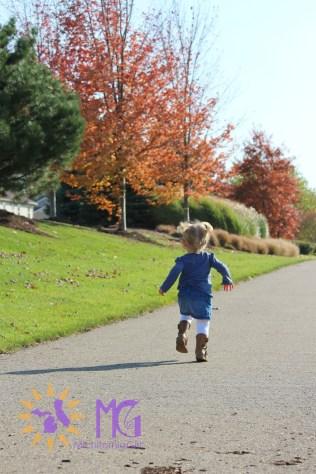 little girl running in the fall