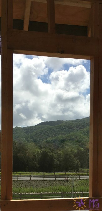 view of clouds and mountain through an open window