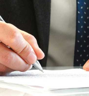 Photo of man signing with pen
