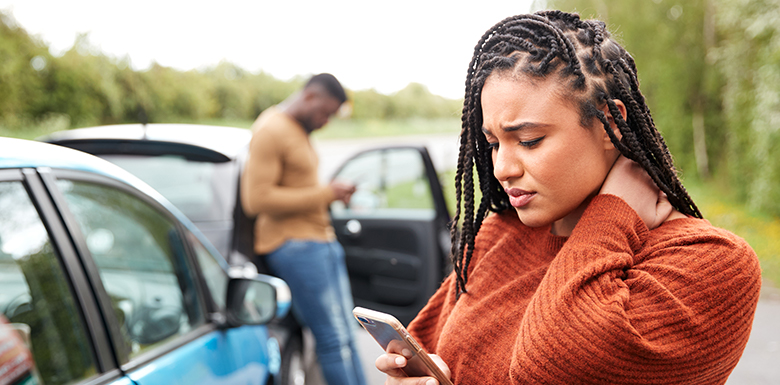 Stressed woman types on phone after car accident