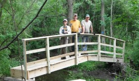 Katherine Hollins, Bill McEachern, and Paul Messing stand on the completed bridge at Kernan Memorial Nature Sanctuary.