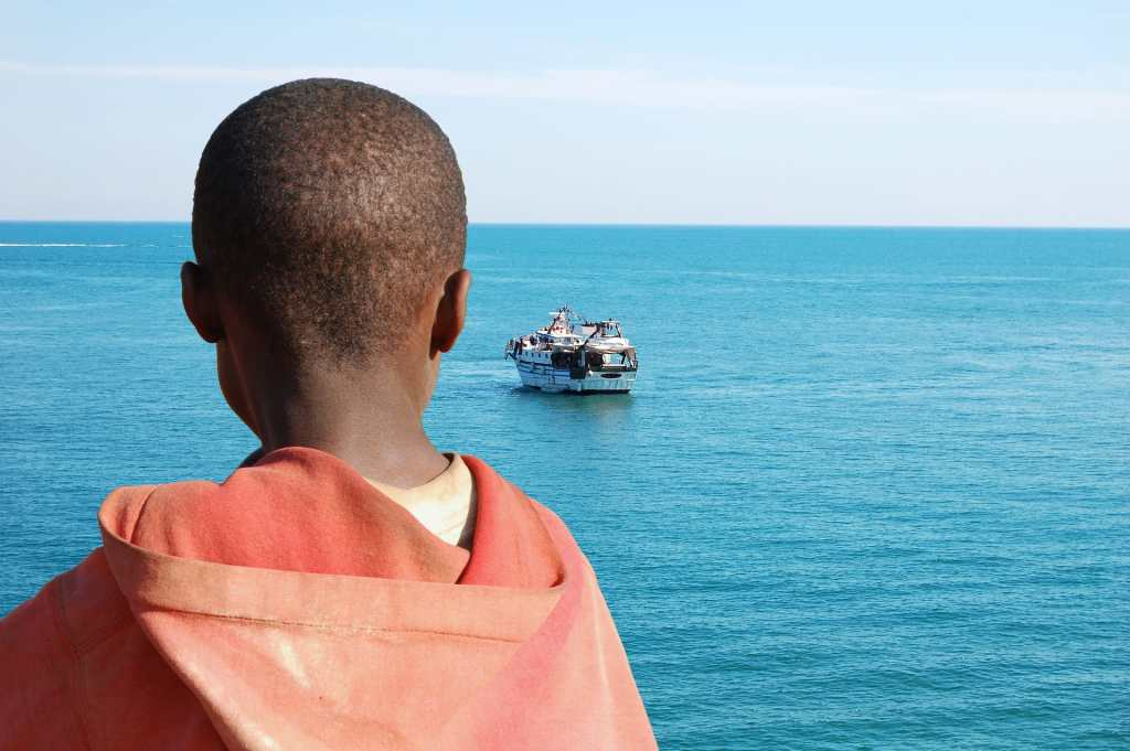 Refugee looking out to sea