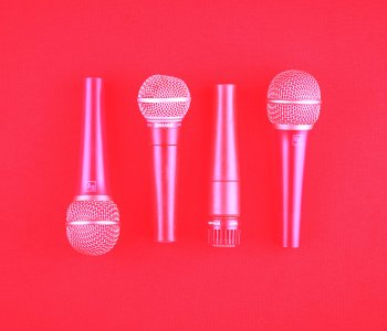 a photo of 4 microphones, laid side by side. The image is taken from above and is coloured pink