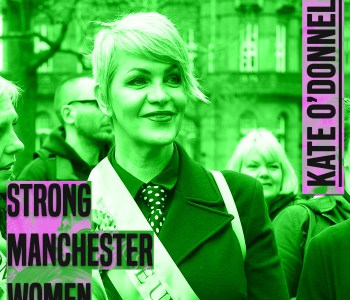 A woman stands in the front of a group of people. She has short, light hair, she is looking ahead and smiling. She is wearing a sash. The photo is from chest up.The image has a green hue to it. to the left of her knees are the words 'strong manchester women' in grey lettering and a thick font in capital letters. In the same style font, next to her right ear are the words 'Kate O'Donnell'