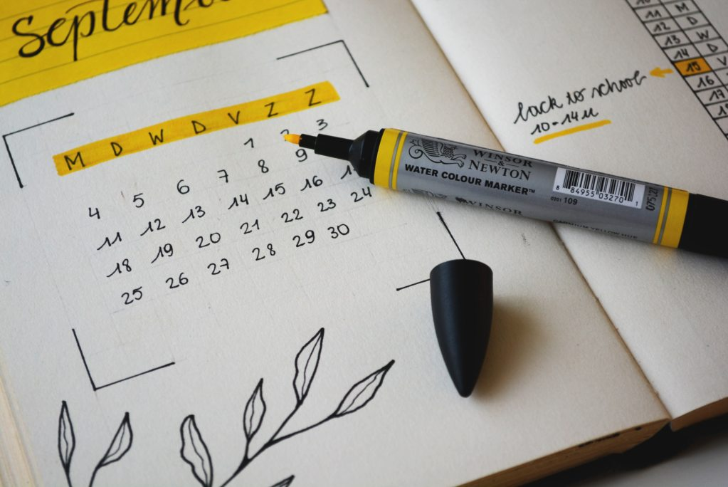a yellow marker highlights a calendar on a notepad