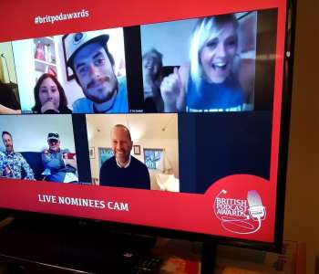 a photo of a tv screen, on the screen is smaller shots of faces. the screen is taken from the bitish podcast award ceremony