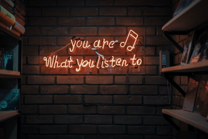 [Image of a brick wall with bookshelves on either side and neon yellow sign with text saying: 'you are what you listen to']