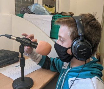 Image of a boy with headphones and a face mask on holding a microphone on a stand