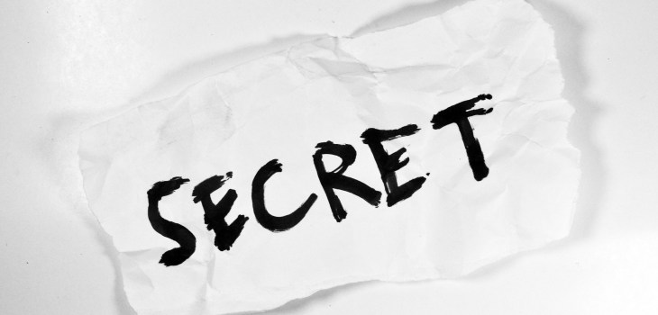 White background with the word secret written on a crumpled piece of paper