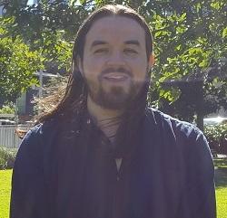 a face on shot of a man. He is smiling, He has a black beard and black shoulder length hair