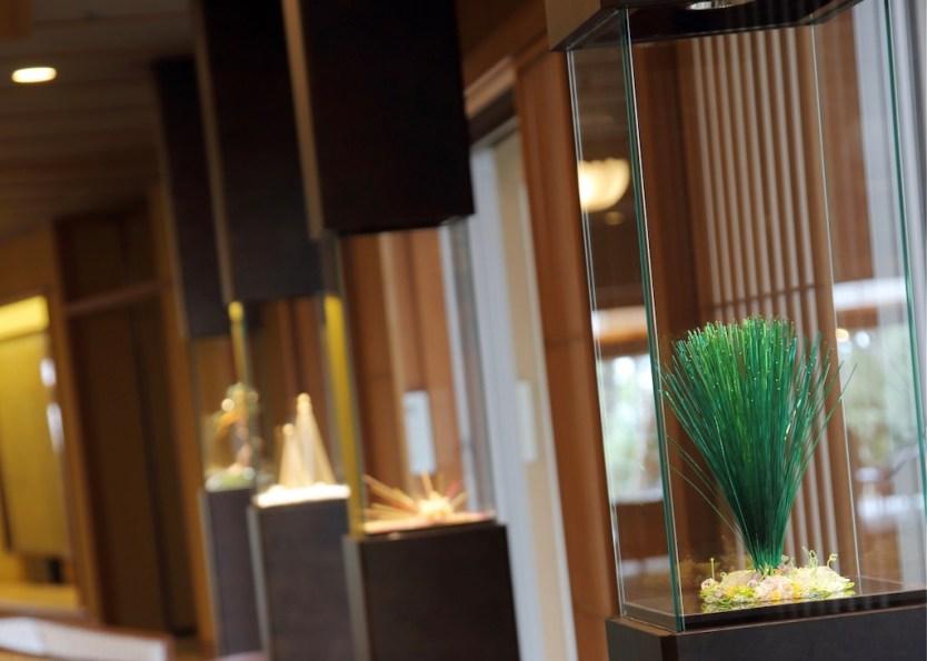 鴨川館ラウンジギャラリーにある、水引アートの常設展示。全9点、松の成長をテーマにディスプレイしています。