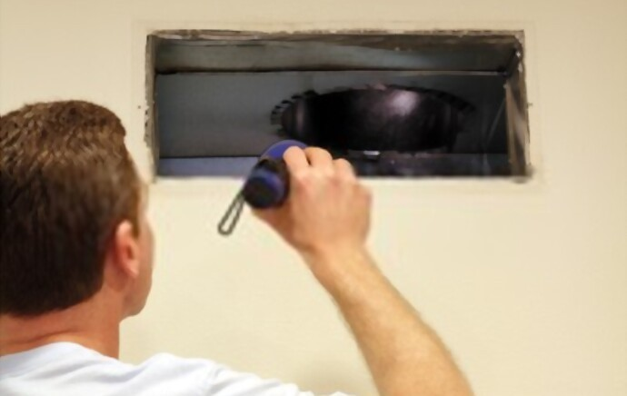 A man looking into his air duct