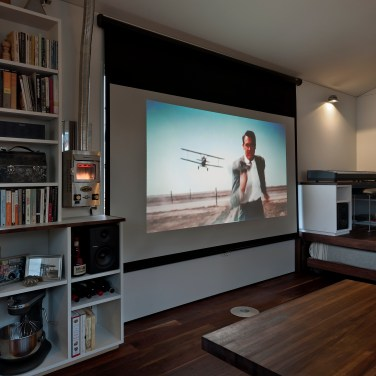 The large window array next to the door is conveniently sized in 9:16 proportion, and a projector screen hanging above it doubles as a shade. A small LED projector affixed near the bookcase displays a 90'' image, accompanied by speakers on either side of the window. A Dickenson marine propane heater appears to the left of the screen.